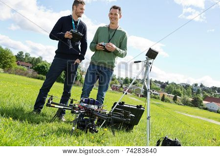 Happy young technicians holding remote controls of UAV helicopter at park