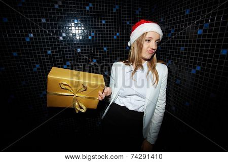 Portrait of fastidious businesswoman in Santa cap holding giftbox