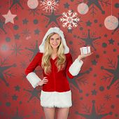 Pretty girl in santa outfit holding gift against orange poster