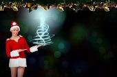 Pretty santa girl presenting with hands against fir branch christmas decoration garland poster