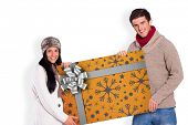 Young couple holding a poster against christmas wrapping paper with bow poster