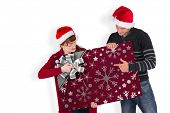 Couple holding a white sign against christmas wrapping paper with bow poster