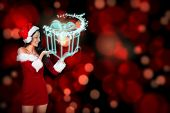 Pretty girl presenting in santa outfit against glowing christmas gift poster