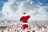 Santa standing on pile of gifts against balcony overlooking city poster