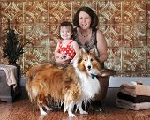A mature woman with her granddaughter and pet.  They've been washing the beautiful collie in a small, copper tub.  He's standing in front of it with feet and lower fur dripping wet. poster