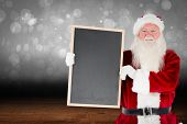 Santa claus showing blackboard against shimmering light design over boards poster