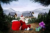 Santa looking through telescope against cute village in the snow poster