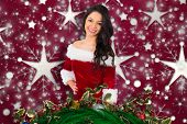 Pretty girl smiling in santa outfit against snowflake wallpaper pattern poster
