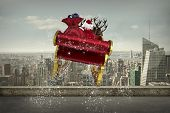 Santa flying his sleigh against balcony overlooking city poster