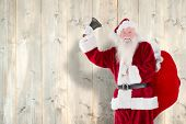 Santa claus ringing bell against pale wooden planks poster