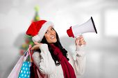 Woman holding some shopping bags against blurry christmas tree in room poster