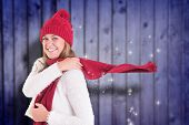 Happy blonde in winter clothes against blurred wooden planks poster