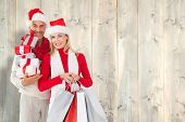 Happy festive couple with gifts and bags against pale wooden planks poster