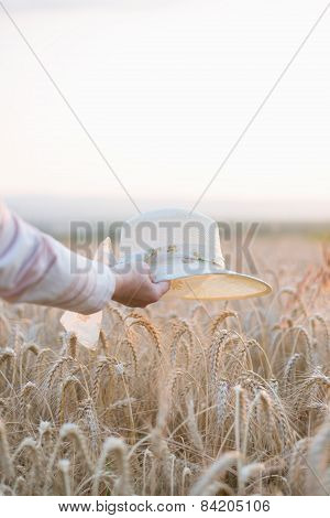 Woman Holding Straw Hat Over Wheat