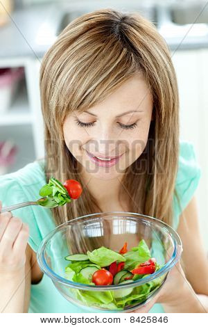 Cute Young Woman Eating A Healthy Salad In The Kitchen