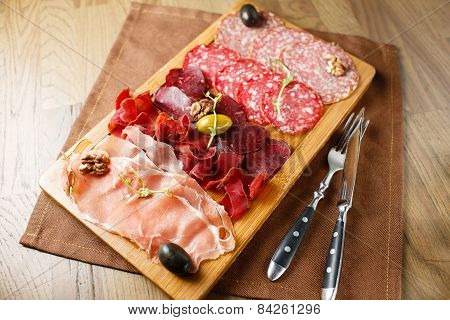 Variety of meats, sausages, salami, ham, olives
