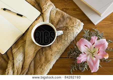 Wooden desk with a cup of coffee, notebook and flower