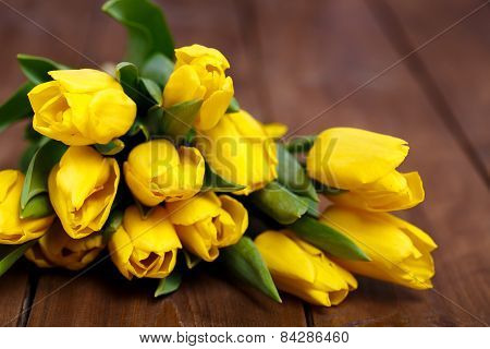 A bouquet of bright yellow tulips on the old wooden floor.