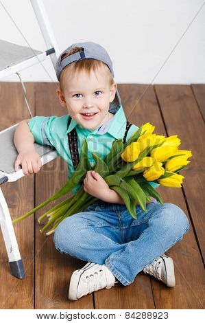 Smiling boy holding a large bouquet of yellow tulips.