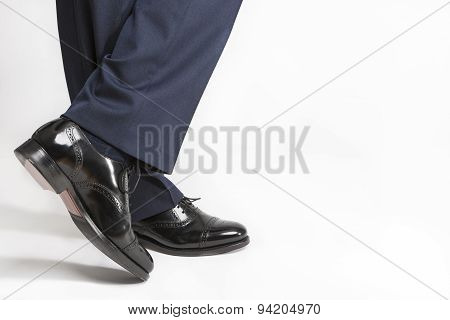 Footwear Concept: Closeup Of Stylish Black Shiny Male Semi-brogue On Crossed Legs Against White