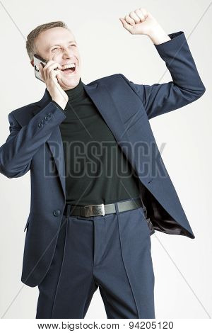 Expressive Handsome Caucasian Man In Elegant Siut Speaking By Cell Phone And Smiling