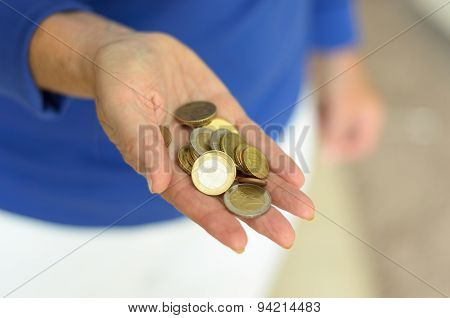 Woman Holding Loose Change In Her Hand