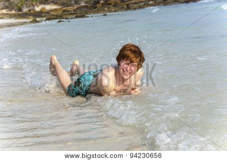 Boy Enjoys Lying In The Spume Of The Tropical Beach