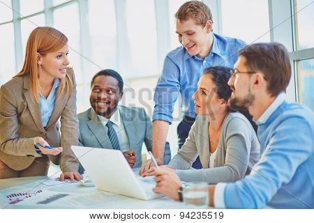 Group of employees looking at confident manager explaining her ideas at meeting