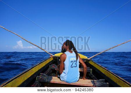 Rasta fisherman in a wooden boat in Port Antonio, Jamaica
