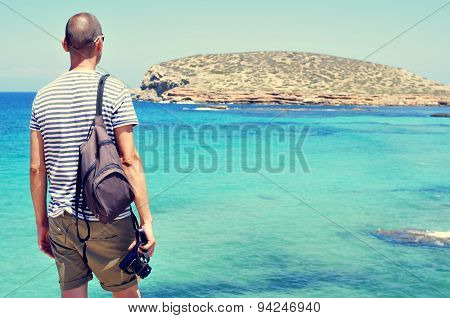 a young man with a camera in his hand looking at the sea and the Illa des Bosc island, in Ibiza island, Spain