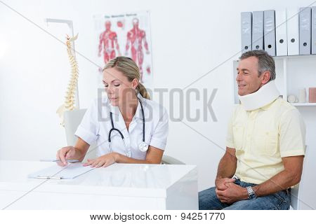 Doctor examining her patient wearing neck brace in medical office