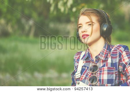 Portrait of pretty attractive hipster girl headphones. Warm toning. The concept of youth fashion. poster