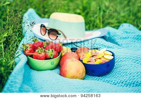 Picnic Sheet With Fruits On The Grass, Hat With Sunglasses On Background