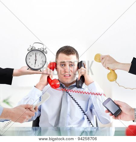 hand holding alarm clock against businessman unable to cope the telephone