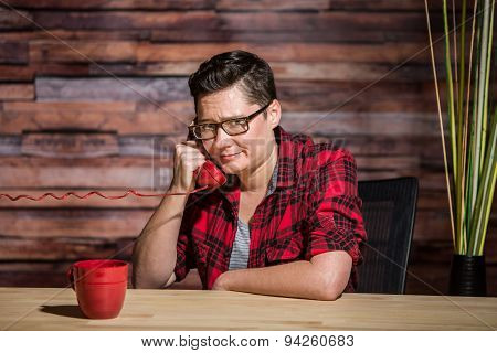 Woman Wearing Casual Red Shirt In Modern Office On Push-button Phone