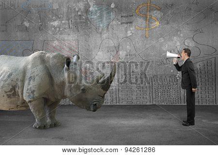 Businessman Using Speaker Against Rhinoceros With Doodles Wall