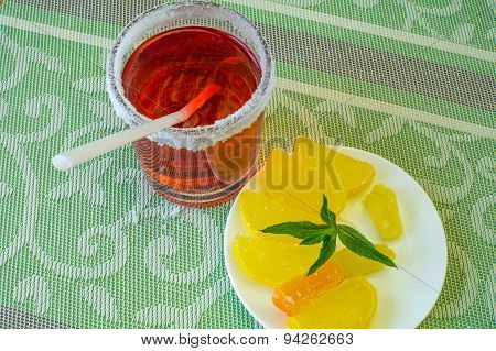 Glass With A Drink And A Saucer With Fruit Candy.