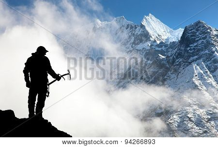 Silhouette Of Man With Ice Axe In Hand And Mountains