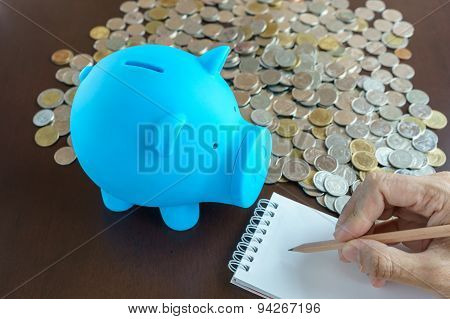 Blue Piggy Bank And Hand Writing On Notepad
