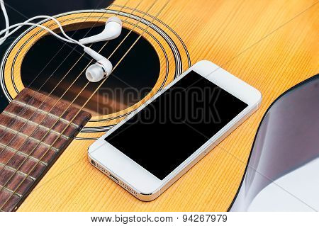 mobile and earphone on guitar,selective focus