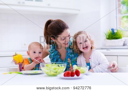 Mother And Children Cooking In A White Kitchen