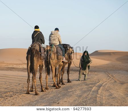 The Arabian Guide With Couple Of Tourist In Sahara Desert