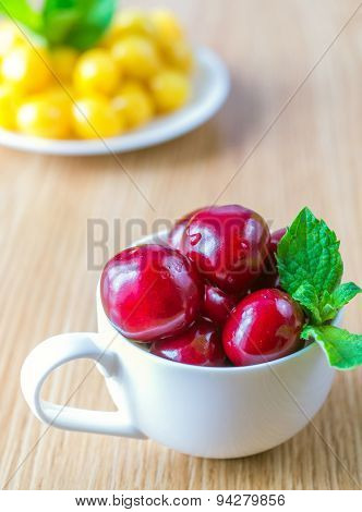 On A Table There Is A Cup With A Sweet Cherry.
