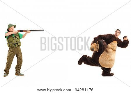Full length portrait of a mature hunter aiming a rifle towards a man in a bear costume isolated on white background