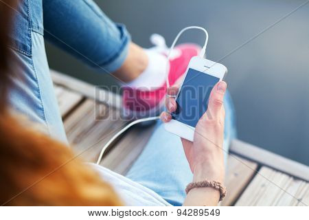 Young woman sitting on pier holding a smartphone.