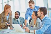 Group of employees looking at confident manager explaining her ideas at meeting poster