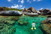 Young woman snorkeling in turquoise tropical water among huge granite boulders at The Baths beach area major tourist attraction on Virgin Gorda, British Virgin Islands, Caribbean poster