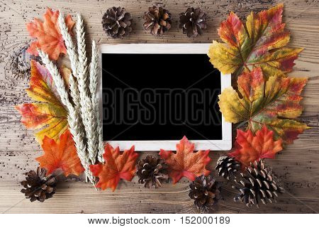 Blackboard With Autumn Or Fall Decoration. Greeting Card For Seasons Greetings. Colorful Leaves, Fir Cone And Barley On Aged Wooden Background. Copy Space For Advertisement Or Free Text