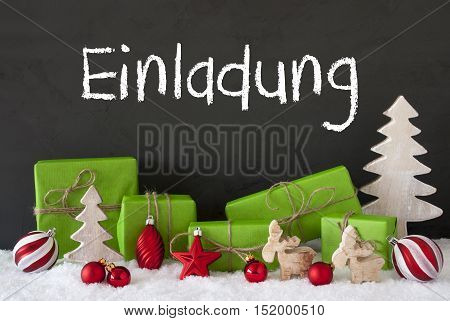 German Text Einladung Means Invitation. Green Gifts Or Presents With Christmas Decoration Like Tree, Moose Or Red Christmas Tree Ball. Black Cement Wall As Background With Snow.