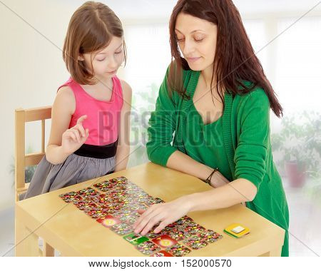 Pensive little girl and her teacher at the table laid out cards with pictures.In a room with a large semi-circular window.
